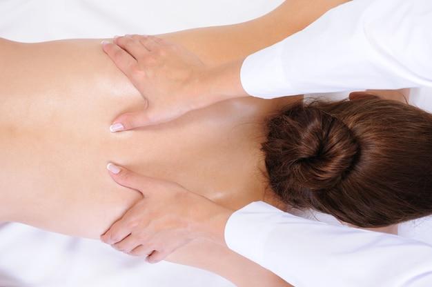 Здоровый массаж спины для молодой женщины - белый фон Бесплатные Фотографии