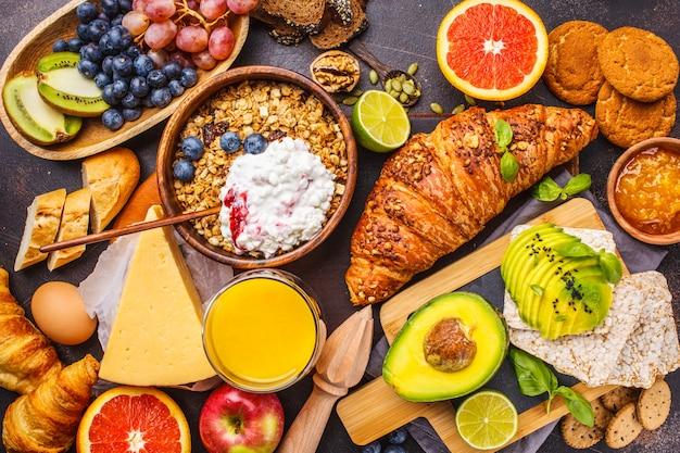 Healthy balanced breakfast on a dark background. muesli, milk, juice, croissants, cheese, biscuits. Premium Photo