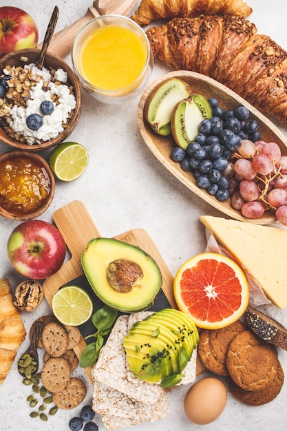 Healthy balanced breakfast on white background. muesli, juice, croissants, cheese, biscuits and fruit, top view. Premium Photo