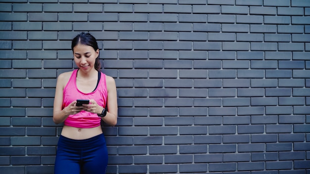 Healthy beautiful young asian athlete woman using smartphone for checking social media Free Photo