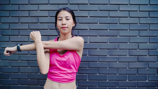 Healthy beautiful young asian athlete women in sports clothing legs warming and stretching her arms Free Photo
