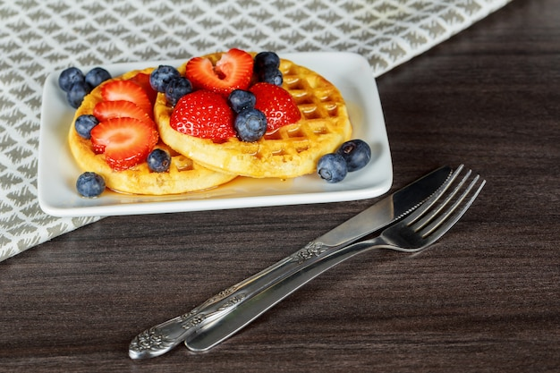 Healthy breakfast: belgian waffles with sour cream, strawberry, raspberry, blueberry Premium Photo