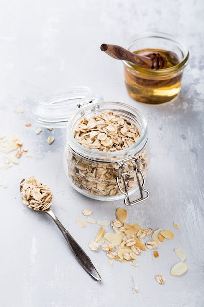 Healthy breakfast concept, oat flakes in glass jar with honey. Premium Photo
