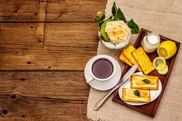 健康的な朝食。一杯のコーヒー(紅茶)、牛乳、バターとサーモンのクラッカー Premium写真