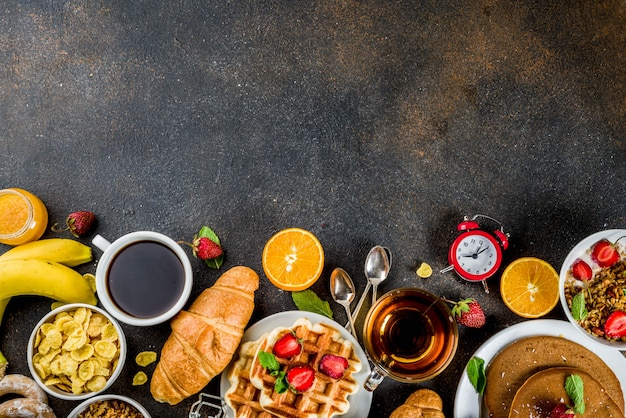 Healthy breakfast eating concept, various morning food - pancakes, waffles, croissant oatmeal sandwich and granola with yogurt, fruit, berries, coffee, tea, orange juice background Premium Photo