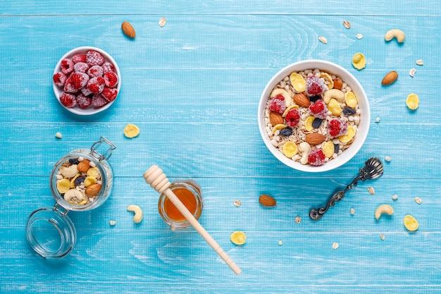 健康的な朝食。新鮮なグラノーラ、ミューズリー、ナッツ、冷凍ベリー。上面図。コピースペース。 無料写真