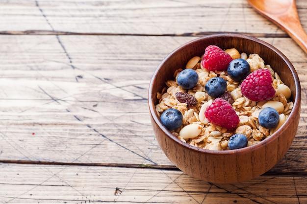 Healthy breakfast. fresh granola, muesli with yogurt and berries on wooden surface Premium Photo