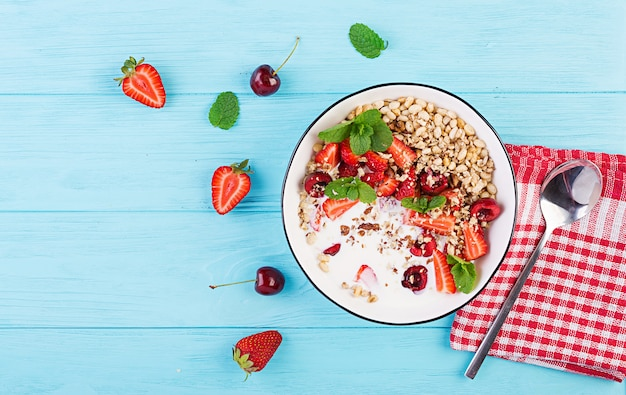 Healthy breakfast - granola, strawberries, cherry, nuts and yogurt in a bowl on a wooden table. vegetarian concept food. top view Free Photo