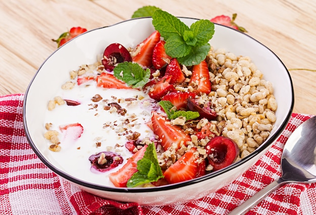 Healthy breakfast - granola, strawberries, cherry, nuts and yogurt in a bowl on a wooden table. vegetarian concept food. Free Photo