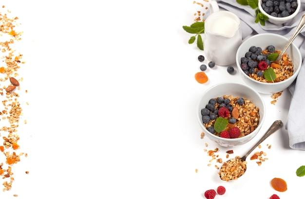 Healthy breakfast -  homemade granola, honey, milk and berries Premium Photo