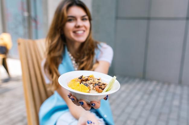 椅子に座っている若い女性の手で健康的な朝食 無料写真