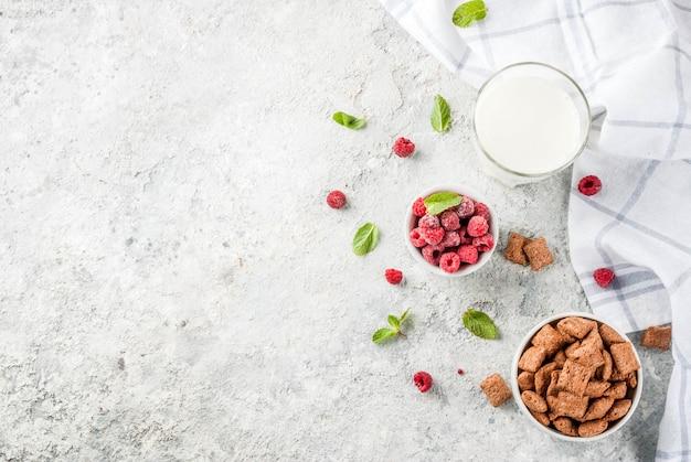 Healthy breakfast ingredients. breakfast cereal, milk or yogurt glass, raspberries Premium Photo
