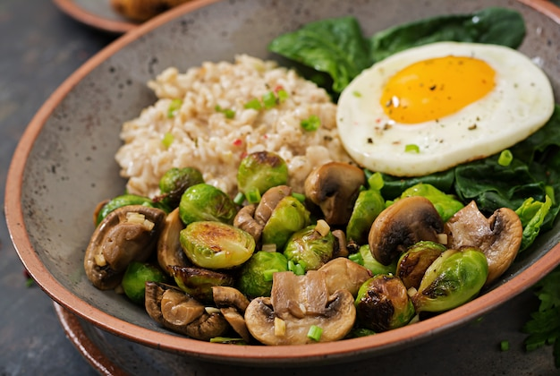 Healthy breakfast. oat porridge, egg and salad of baked vegetables - mushrooms and brussels sprouts.. Free Photo