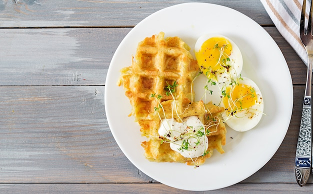 Healthy breakfast or snack. potato waffles and boiled egg on grey wooden table. top view. flat lay Premium Photo