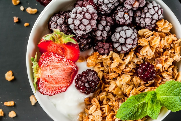 Healthy breakfast. summer berries and fruits. homemade greek yogurt with granola, blackberries, strawberries and mint.  black stone table, with the ingredients. top view Premium Photo