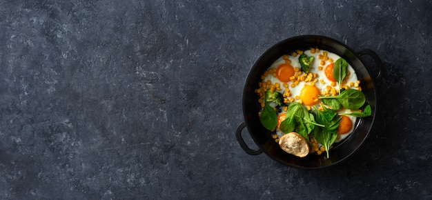 Healthy breakfast table with fry pan eggs with spinach and corn on dark stone background top view Premium Photo