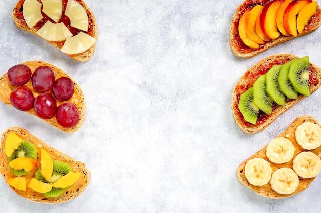 ピーナッツバター、いちごジャム、バナナ、ブドウ、ピーチ、キウイ、パイナップル、ナッツの健康的な朝食トースト。コピースペース Premium写真