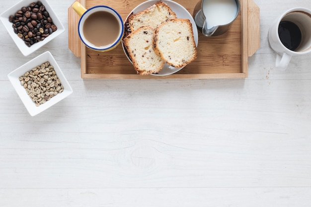 Healthy breakfast with coffee beans and bread in tray Free Photo