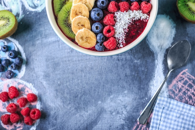 Healthy breakfast with delicious acai smoothie in bowl on chalk board Premium Photo