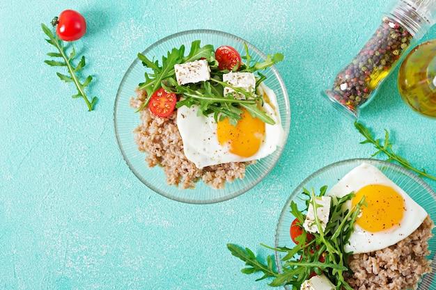 Healthy breakfast with egg, feta cheese, arugula, tomatoes  and buckwheat porridge on light background. proper nutrition. dietary menu. flat lay. top view Free Photo