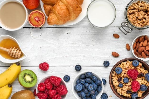 Здоровый завтрак с мюсли мюсли, фруктами, ягодами, орехами, круассаном и чашкой кофе Premium Фотографии
