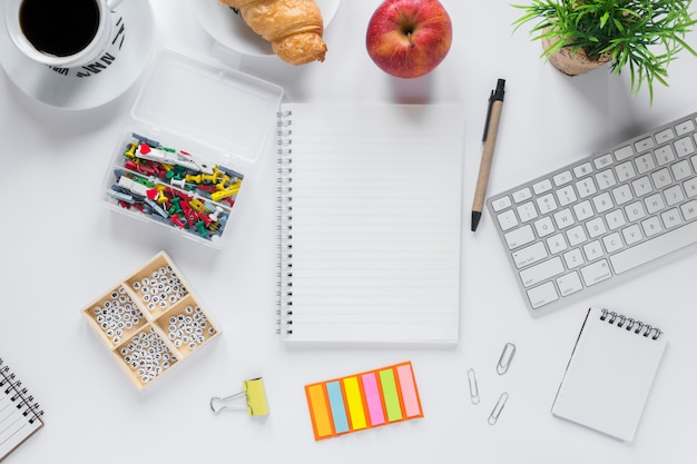 Healthy breakfast with office stationeries on white backdrop Free Photo