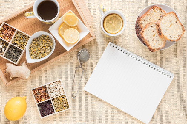 Healthy breakfast with variety of herbs; lemon; strainer; bread; ginger and blank spiral notepad Free Photo