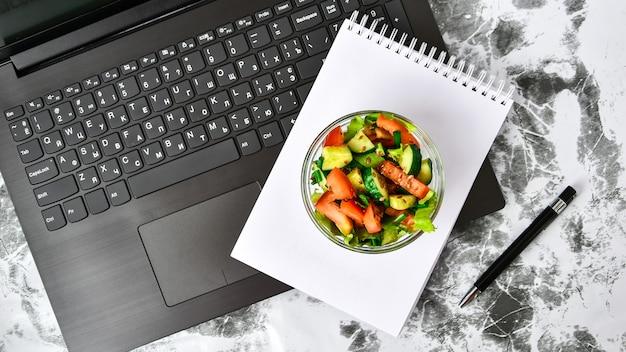 オフィスでのヘルシーなビジネスランチスナック、野菜サラダ、ペンで空のノート Premium写真