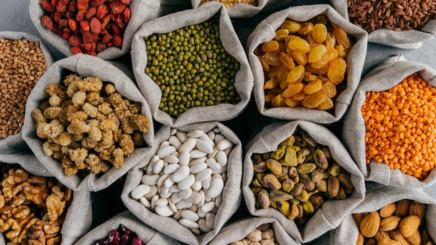 Healthy cereals and dried fruit. close up top view of small bags with dry legumes seeds. different types of beans. natural grains. Premium Photo
