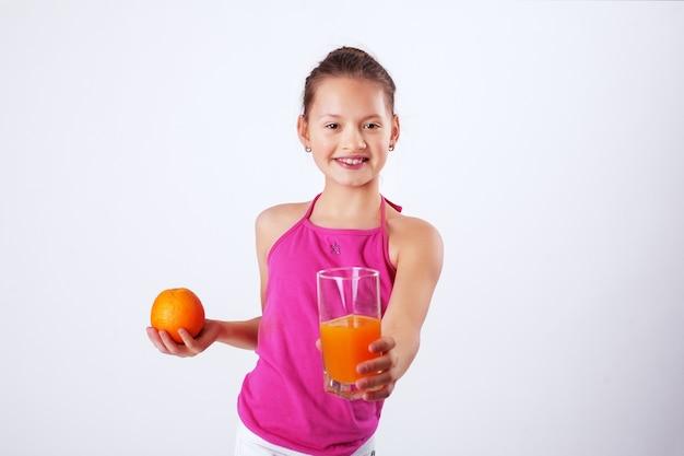 Здоровый ребенок с соком и апельсином. здоровая пища Premium Фотографии