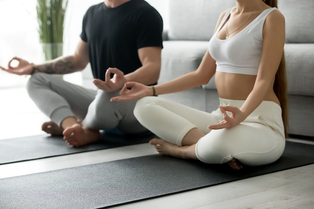 Healthy couple doing home yoga practicing meditation together, Free Photo