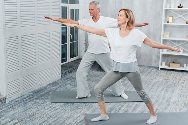 Healthy couple performing exercising on yoga mat at home Free Photo