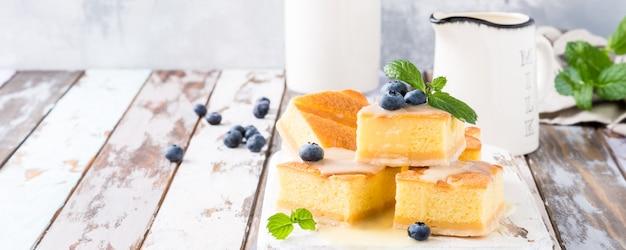 Healthy dessert. homemade pudding cake with custard cream and blueberries. Premium Photo