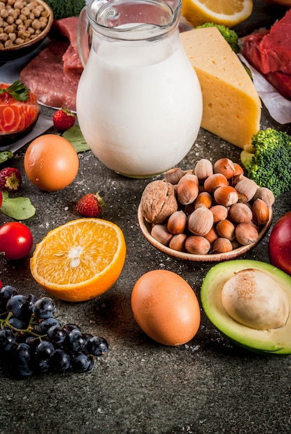 Healthy diet background. organic food ingredients, superfoods: beef and pork meat, chicken filet, salmon fish, beans, nuts, milk, eggs, fruits, vegetables Premium Photo