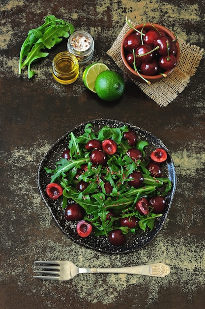 Healthy dietary salad with sweet cherries and arugula. fitness salad. raw diet. Premium Photo