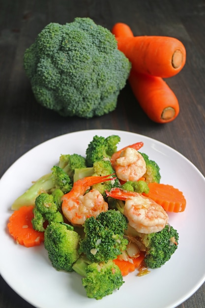 Healthy dish of prawn stir fried with broccoli and carrot served on white plate Premium Photo
