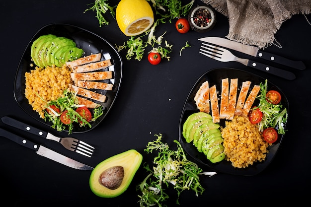 Healthy dish with chicken, tomatoes,  avocado, lettuce and lentil on dark  background. Premium Photo