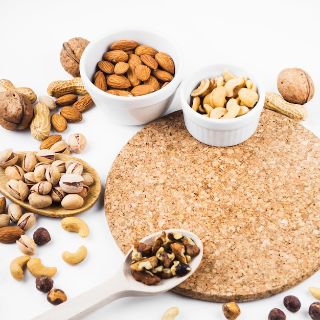 Healthy dried fruits bowl and spoon with cork coaster on white background Free Photo