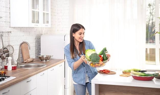 健康的な食事のコンセプトです。果物と野菜を台所で若い美しい女性。ビーガンフード 無料写真