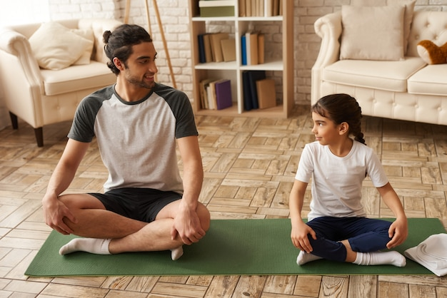 Healthy father and daughter sit in lotus pose on carpet. Premium Photo