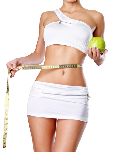 Healthy female body with apple and measuring tape. healthy fitness and eating lifestyle concept. Free Photo