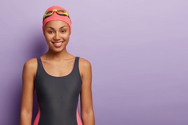 健康な女性のスイマーはピンクのキャップ、ゴーグル、水着を着て、プールでのトレーニングの準備をします 無料写真