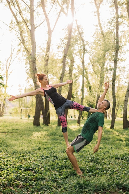 Healthy fit couple doing acro yoga on grass Free Photo
