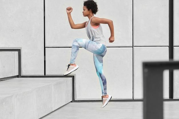 건강한 여성은 계단을 오르고, 편안한 옷과 트레이너를 입고, 조깅 운동을하고, 도시 환경에서 스포츠를하고, 빠르고, 옆으로 포즈를 취합니다. 웰빙과 결단력 개념 무료 사진