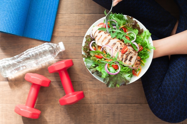 Healthy and fitness food. chicken salad dish with fitness equipments Premium Photo