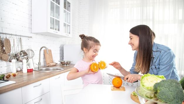 自宅で健康食品。台所で幸せな家族。母と子の娘が野菜や果物を準備しています。ビーガンフード 無料写真