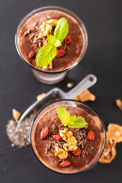 Healthy food concept chia seeds, chocolate milk pudding with goji and dried walnuts in small glass on black slate board background Premium Photo