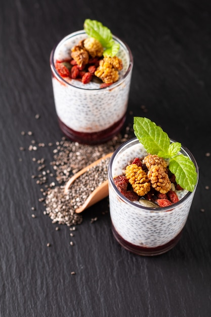 Healthy food concept chia seeds, milk pudding with goji, white mulberry and mix dried seeds in small glass on black slate board background Premium Photo