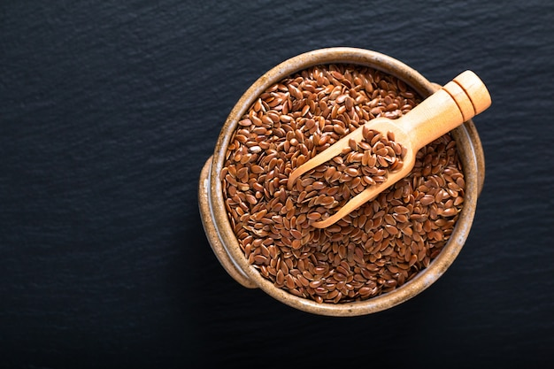 Healthy food concept organic flax seeds in ceramic bolw on black slate board with copy space Premium Photo