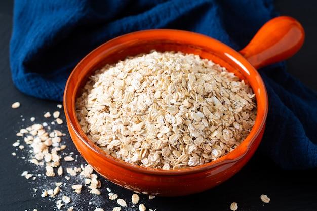 健康食品のコンセプトオーガニック全粒巻き麦、黒スレート石に青いナプキンとオレンジボウル Premium写真